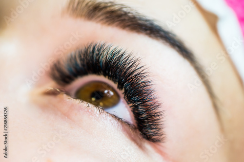 The master of eyelash extensions, the beautician increases eyelashes to the clie Canvas Print