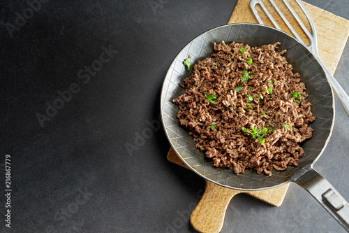 Fototapeta Minced meat fried on pan with green chives obraz