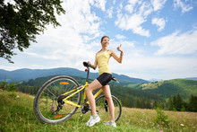 Young Happy Woman Cyclist Standing On A Grassy Hill, Showing Thumbs Up, Holding Yellow Mountain Bicycle, Enjoying Summer Day In The Mountains. Outdoor Sport Activity, Lifestyle Concept