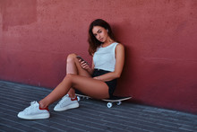 Portrait Of A Sensual Hipster Girl Dressed In Shorts And T-shirt Sitting On Skateboard Holds A Smartphone While Leaning On A Wall.