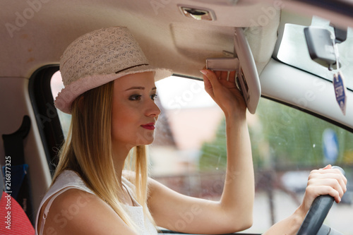 Fotografia, Obraz  Distracted woman driving her car looking in mirror