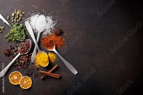 Foto op Plexiglas Aromatische Various spices spoons on stone table
