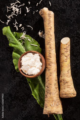 Horseradish root and grated horseradish on black background.