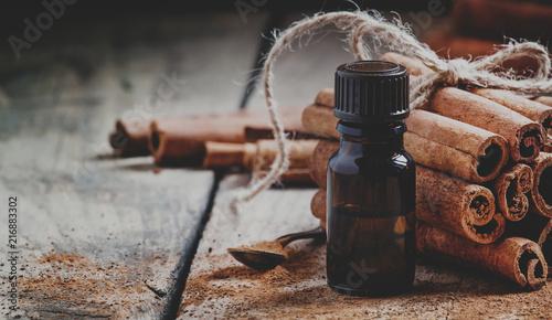 Photo Essential cinnamon oil in a small bottle, ground cinnamon and cinnamon sticks on