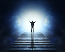 A Man In A Suit With Arms Outstretched On A Stone Staircase To The Clouds And Light. Stairway To Heaven.