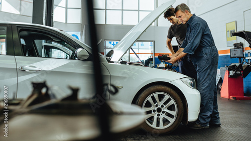 Obraz Mechanics inspecting a car using an electronic device - fototapety do salonu