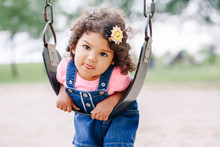 Portrait Of Happy Smiling Little Latin Hispanic Toddler Girl Swinging On Swings At Playground Outside On Summer Day. Happy Childhood Lifestyle Concept. Toned With Film Pastel Faded Filters Colors.