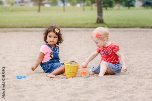 Fototapeta Portrait of two cute Caucasian and hispanic latin toddlers babies children sitting in sandbox playing with plastic colorful toys