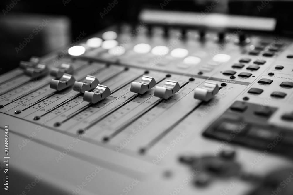 Fototapeta Sound recording studio mixing desk. Music mixer control panel. Closeup. Selective focus. Black and White image