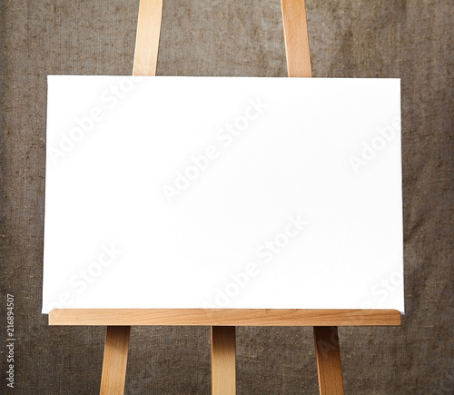 Photo  pure white synthetic canvas stretched on a wooden stretcher standing on a wooden easel for artists