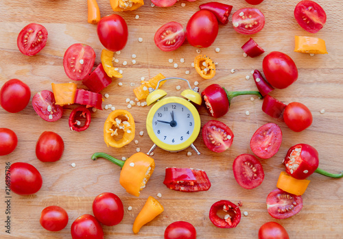 Fotobehang Kruiderij yellow and red peppers, tomatoes with alarm clock on wooden table. Above view