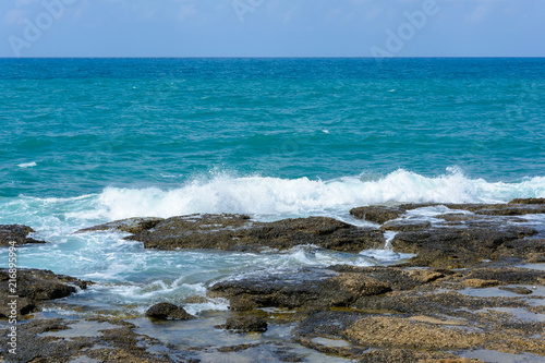 Fotobehang Water view of the Mediterranean horizon and the waves with foam breaking on the coastal stones