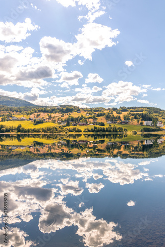 Deurstickers Blauwe hemel Norwegian mountain lake summer landscape. Clouds reflecting in the crystal clear water surface.