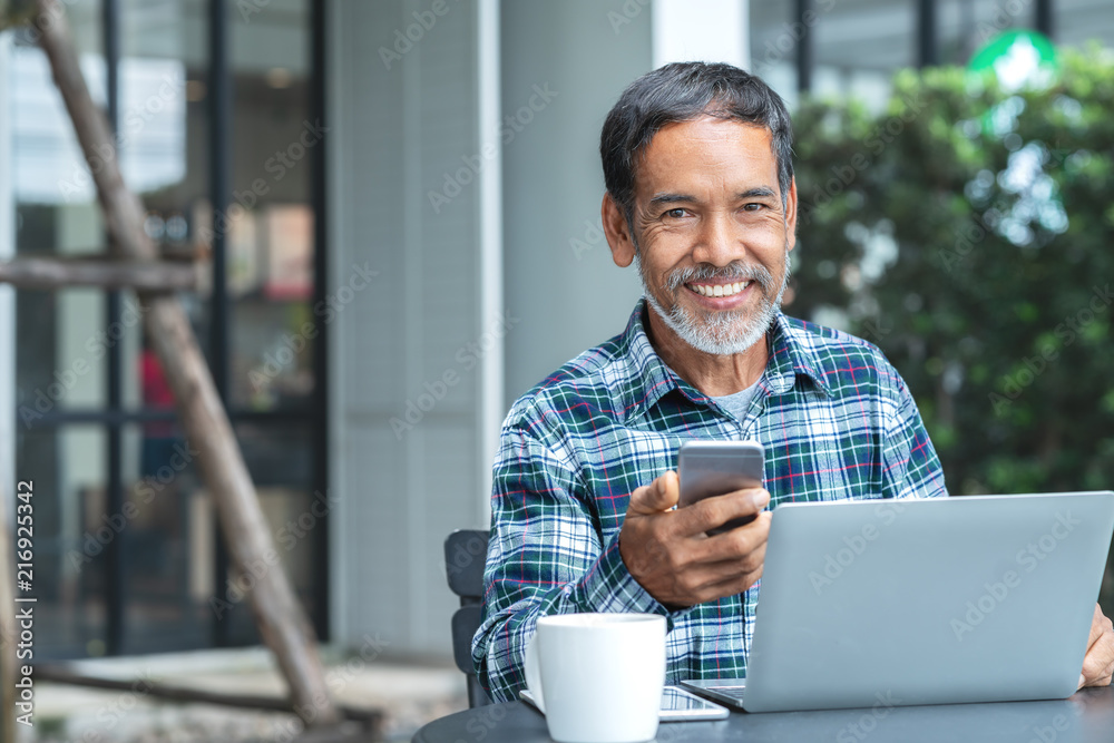 Fototapeta Smiling happy mature asian man with white stylish short beard using smartphone gadget serving internet at coffee shop cafe outdoor. Old indian or hispanic man using network technology with confident.