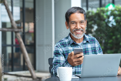 Fotografia, Obraz Smiling happy mature asian man with white stylish short beard using smartphone gadget serving internet at coffee shop cafe outdoor