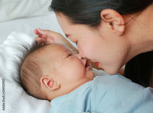 Fototapeta Close up mother kissing baby boy lying on the bed. obraz