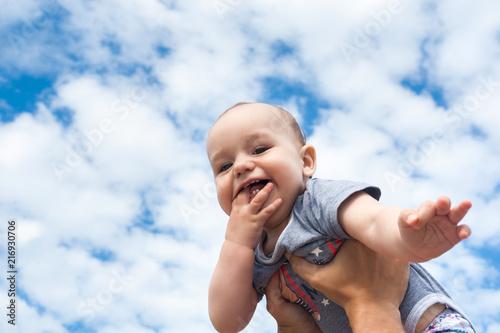 Fototapeta Happy kid on a background of blue sky and clouds obraz na płótnie
