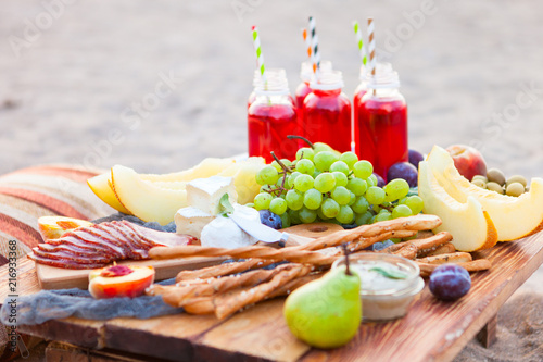 Autocollant pour porte Pique-nique Picnic on the beach at sunset in the style of boho. Concept outdoors evening healthy dinnner with fruit and juice