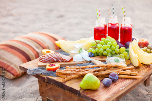 Foto auf Leinwand Picknick Picnic on the beach at sunset in the style of boho. Concept outdoors evening healthy dinnner with fruit and juice