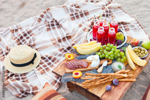 Stickers pour portes Pique-nique Picnic on the beach at sunset in the style of boho. Concept outdoors evening healthy dinnner with fruit and juice