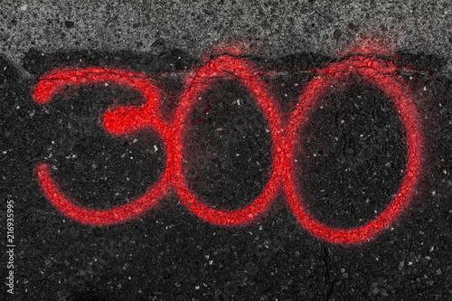 Fotografia  Dreihundert Rote Ziffern auf Asphalt