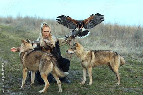 Photo  Beautiful northern warrior viking woman with traditional makeup with wolves and Harris Hawk (Parabuteo unicinctus)