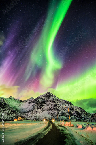 Poster Aurore polaire Aurora Borealis (Northern lights) explosion over mountains and rural road