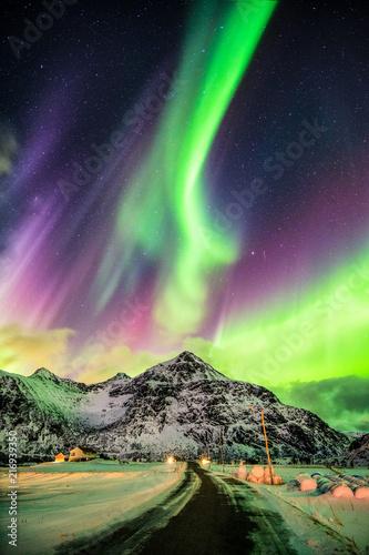 Foto auf Gartenposter Nordlicht Aurora Borealis (Northern lights) explosion over mountains and rural road