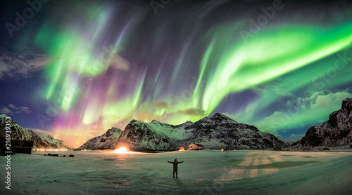 Foto  Aurora borealis (Northern lights) over mountain with one person