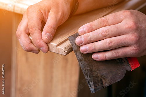 Fotografía  Close-up A carpenter in work clothes restoring a wood with  a spatula on a wooden table