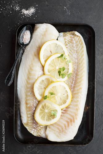 Raw cod fillets with lemon slices on a black baking tray Fototapeta