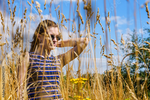 Portrait of a beautiful young girl in sunglasses in a field of dry yellow grass