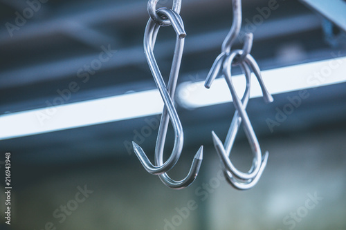 Photo Meat hooks hanging in a slaughterhouse.