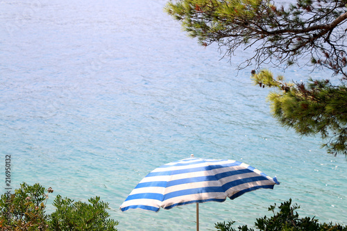 Blue and white striped parasol on the beach, with trees around and turquoise sea in the background.