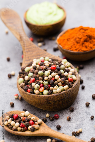 Tuinposter Kruiderij Peppercorn mix in a wooden bowl on grey table.
