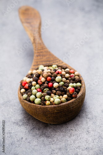 Fotobehang Kruiderij Peppercorn mix in a wooden bowl on grey table.