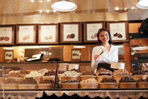 Carta da parati Chocolate Store. Female Seller In Confectionery Shop.