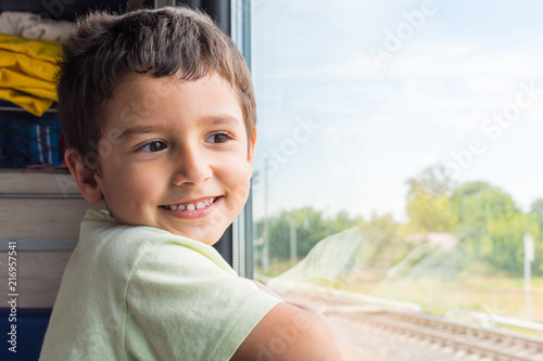 cute cheerful boy goes to rest on the train Fototapet