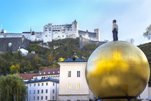 "View Of Castle Hohensalzburg And Monument To Paul Fuerst ""Sphere"" Is A Huge Golden Ball On Which Stands A Small Man - Symbol Of Sweets (sculptor Stephan Balkenhol), Salzburg, Austria"