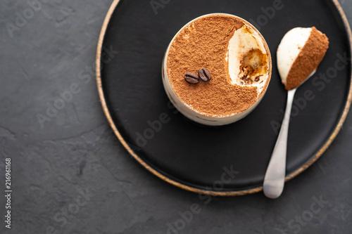 Fototapeta Delicious Italian dessert tiramisu, chocolate, cocoa and coffee beans on a black background. Top view with copy space. obraz