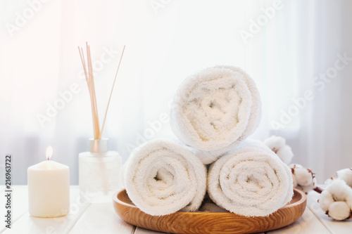 Poster Spa Clean white towels on the wooden tray, candle and aroma diffuser.