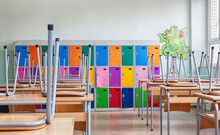 Empty Classroom With Colorful Lockers And Raised Chairs On The Tables