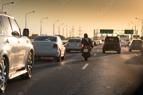 Obraz Traffic jam on a hot summer evening. Highway and road junction. Sunset cars and moto - fototapety do salonu