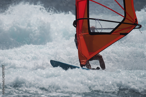 Windsurfer surfing the wind on waves in ocean sea
