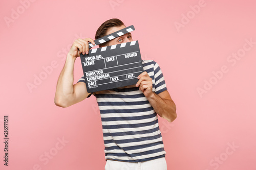 Portrait of young man wearing striped t-shirt holding classic black film making clapperboard isolated on trending pastel pink background Canvas Print