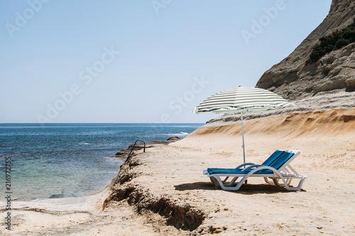 Two blue deck chairs with a beach umbrella with green stripes in Malta / Two blue deck chairs with a beach umbrella with green stripes in a lonely beach.