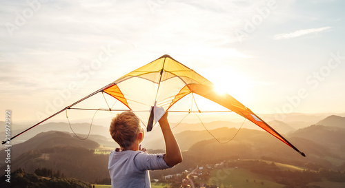 Fotografia  Boy starts to fly a kite over the mountain hills at sunset time