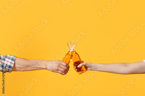 Fotografia Close up cropped of woman and man two hands horizontal holding lager beer glass bottles and clinking isolated on yellow background