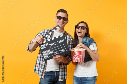 Young laughing couple woman man in 3d glasses watching movie film on date holding classic black film making clapperboard bucket of popcorn isolated on yellow background Canvas Print
