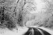 Winter Road With Snow On The Ground. Travel In Difficult Way To Enjoy The Colder Season. White Image With Black Asphalt In Contrast. Drive And Travel Concept